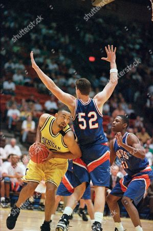 Stock Picture of Michigan's Juwan Howard, left, tries driving around Pepperdine's Derek Noether (52) during the first half of their first round of the NCAA Midwest Regional tournament game, in Wichita, Kan. At right is Pepperdine's Dana Jones