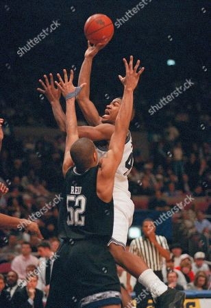 Dickey Simpkins, of Providence, takes a shot over defending Don Reid, of Georgetown, during the second half of their Championship Game on at Madison Square Garden in New York. Simpkins scored 16 points as Providence beat Georgetown, 74-64, to win their first Big East Championship