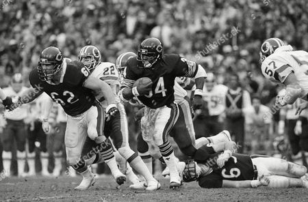 Chicago Bears running back Walter Payton (34) with Bears defender Mark Bortz (62) in front gets some yardage in action against the Washington Redskins on in Washington. Skins Curtis Jordan (22) is shown