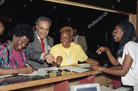 Dr. Benjamin Hooks, center, executive director of the NAACP, registers for the 78th annual NAACP convention in New York, with Eva Snow, State Youth Advisor of New Jersey, left, and Barbara Gilmore, State Youth Advisor of Lakewood, New Jersey, right. Hooks said one of the prime focuses of the convention will be strategy to defeat the nomination of conservative judge Robert H. Bork to the U.S. Supreme Court