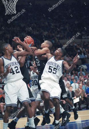 Eric Williams (55) of Providence tangles with Don Reid (52) of Georgetown, as Dickey Simpkins (42) and Michael Brown (30) of Providence look on in the first half of the Big East final, at New York's Madison Square Garden. Providence won, 74-64