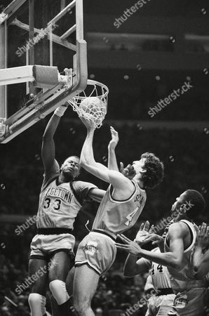Georgetown's Patrick Ewing (33) dunks the ball over Syracuse's Rony Seikaly (4) during semifinals of the Big East Tournament at New York's Madison Square Garden
