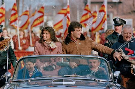 Doug Flutie, Laurie Fortier Heisman trophy winner Doug Flutie of Boston College reaches out to touch fans along the motorcade route as he fiancee Laurie Fortier sits at his side, during a parade held in his honor in Natick, Mass., his hometown