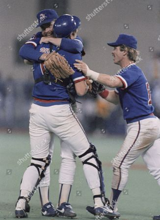 Chicago Cubs' pitcher Rick Sutcliffe is hugged by catcher Jody Davis as third baseman Ron Cey moves in after the Cubs clinched the National League East Championship on against the Pittsburgh Pirates. The Cubs won the game 4-1 in Pittsburgh