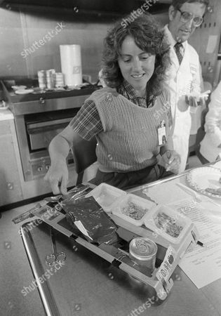 Stock Image of Christa McAuliffe, Charles Borland Teacher, Christa McAufille, checks out the space food as Charles Borland explains how its packaged and prepared in space, at the Johnson Space Center in Houston, Texas, . The teacher started her four month training program for the January 1986 flight today