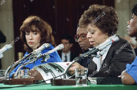 Clarence Thomas' former secretary Diane Holt pages through phone log detailing calls made by Anita Hill to Thomas during testimony before the Senate Judiciary Committee on Capitol Hill, Washington, . J.C. Alvarez, a former aide to Thomas, and Nancy Fitch, a former assistant to Thomas at the EEOC, center, look on