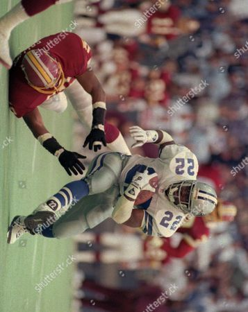 Stock Image of EMMITT SMITH Dallas Cowboys running back Emmitt Smith (22) runs over Washington Redskins line backer Andre Collins for a gain of 18 yards in the second quarter in Irving, Texas