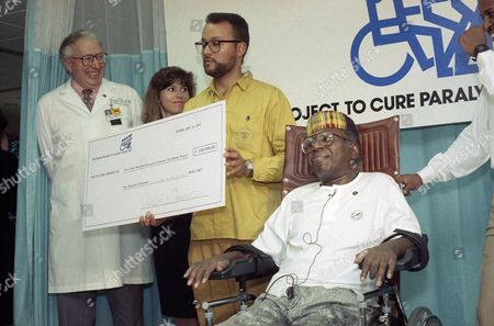 Curtis Mayfield, Richard Bunge, Christine Chambers, Tracy Mayfield Rock and Roll Hall of Famer Curtis Mayfield of Atlanta is shown at the Miami Project To Cure Paralysis as he presented a check to the center for $100,000, . Mayfield was paralyzed last August in a stage accident. Mayfield's son Tracy, center, presents the check to Richard P. Bunge, scientific director of the project. Christine Chambers looks on in between them