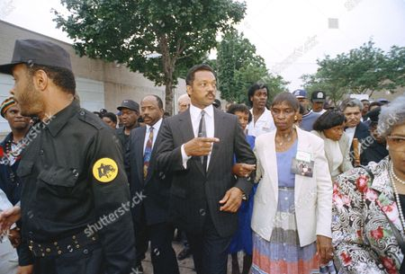 The Rev. Jesse Jackson escorts Shirley Hughes along 25th Street in Milwauke, as he leads hundreds of supporters in a march from the apartment building of Jeffrey L. Dahmer to St. Luke's Emmanuel Baptist Church. The march was in support of the families of the victims whose bodies were found in Dahmer's apartment on July 22. Hughes is the mother of victim Tony Hughes
