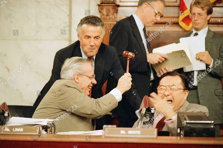 Rep. William Broomfield, R-Mich., left, pretends to rep Sen. Daniel Inouye, D-Hawaii, chairman of the Senate project panel investigating the Iran-Contra affair, on the head while Sen. Paul Sarbanass, D-Md., watches during a break in the Iran-Contra hearings on Capitol Hill in Washington . The committee heard testimony from Attorney General Edwin Meese III