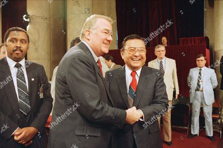 Attorney Gen. Edwin Meese III, left, and Sen. Daniel K. Inouye, D-Hawaii, chairman of the Senate Iran-Contra committee, exchange greetings before the resumption of hearings on Capitol Hill in Washington