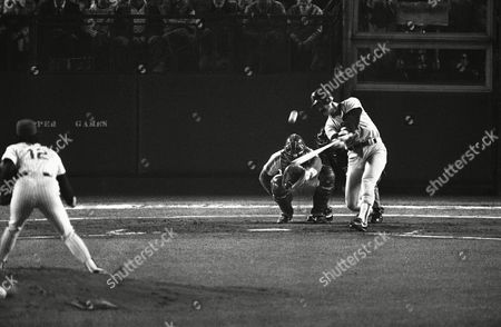Boston Red Sox Dwight Evans connects for a leadoff homerun in the second inning of the seventh game of the World Series at New York's Shea Stadium at night, in New York. Watching the plays are Mets catcher Gary Carter and homeplate umpire John Kibler