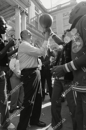Mayor Ed Koch learns a few basketball tricks from Harlem Globetrotter Curly Neal outside New York's City Hall on in New York. Koch was named an honorary Globetrotter