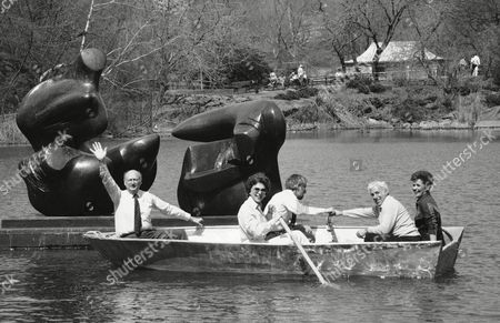 """Mayor Ed Koch waves form a row boat on in New York's Central Park as he passes the Henry Moore sculpture entitled """"Two Piece Reclining Figure: Points"""" that was donated by George and Virginia Ablah of Wichita, Kansas. The two ton work of art is estimated to be worth approximately $1,000,000. The Ablahs can be seen in the boat, at right, with Koch at far left. Bess Myerson, N.Y. cultural affairs commissioner, is shown at center next to N.Y. Park Commissioner Henry Stein"""