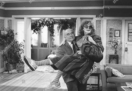 "Actor Ed Asner carries actress Eileen Brennan onto the set of their newly completed TV pilot called, ""Off the Rack,"" during a press conference, in Los Angeles announcing Brennan?s return to television after her accident in 1982 when she was struck by an automobile. Miss Brennan said the anticipation of getting back before the camera was therapy for her during her long months of recuperation from the near-fatal accident"