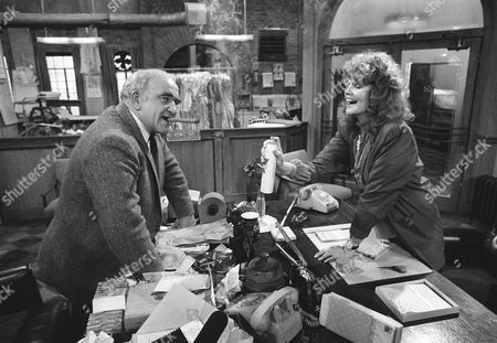 "Actress Eileen Brennan and actor Ed Asner reenact a scene from their upcoming TV pilot called ""Off the Rack"" on the set, in Los Angeles. In the film Asner and Miss Brennan become reluctant partners in a clothing manufacturing company after her husband (Asner's partner) dies. Here, Brennan sprays air freshener at Asner as he smokes a cigar. The film is the first for Miss Brennan since her near-fatal accident in 1982 when she was struck by a car"