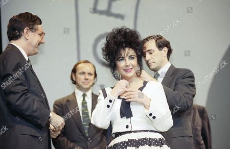 Actress Elizabeth Taylor holds a small Faberge Egg Pendant around a necklace that was given to her by Malcolm Forbes, Jr., left, during the 75th anniversary celebration of Forbes Maganize at UCLA on in Los Angeles. Placing the pendant around Taylor is Kip Forbes. Bob Forbes is at rear