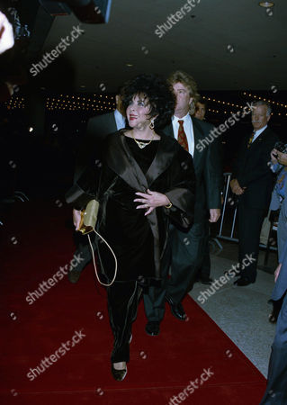 "Superstar Elizabeth Taylor attends a gala Hollywood benefit preview of Andrew Lloyd Webber's newest musical, ""Sunset Boulevard,"" in the Century City district of Los Angeles, on . Taylor's husband Larry Fortensky is behind her and to the right"