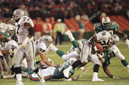 Eric Dickerson, Marco Coleman, Dwight Hollier Los Angeles Raiders runningback Eric Dickerson (29) goes for short yardage as he gets by Miami Dolphins linebacker Marco Coleman (90) with teammate Dwight Hollier (50) rushing in for an assist in first half action football, Miami, Fla