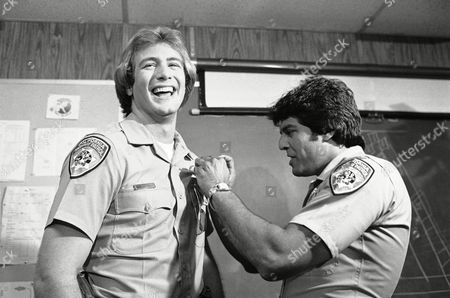 """Erik Estrada, Tom Reilly Erik Estrada, right, star of NBC's """"Chips,"""" pins a badge on the newest member of the cast, Tom Reilly, who joins the cast in place of departing Larry Wilcox, during a media briefing in Los Angeles on . Reilly will portray Estrada's partner, Bobby """"Hot Dog"""" Nelson"""