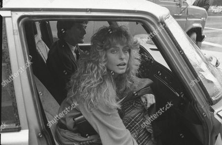 Actress Farrah Fawcett enters a car with an unidentified companion after testifying at the divorce property settlement trial involving her and her estranged actor-husband Lee Majors