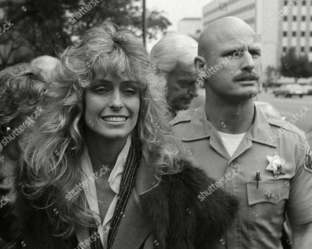 Actress Farrah Fawcett leaves Los Angeles Superior Court following Judge Harry Schaefer's decision that the $2.5 million home of Ms. Fawcett and her estranged husband Lee Majors is community property, . At right is an unidentified sheriff's deputy
