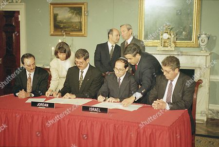 Jordan-Israel peace 1993 Fayez Tarawneh, Jordan's ambassador to the U.S., seated left, and Elyakim Rubinstein, head of the Israeli delegation to the Jordan-Israel peace talks, sign an agreement at the State Department in Washington setting the framework for resolving long-standing differences between them. Secretary of State Warren Christopher, standing right, talks to Victor Posuvaluk of the Russian Foreign Ministry during the signing. Others are unidentified aides