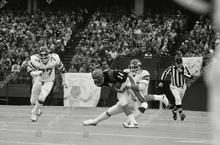 Cincinnati Bengals quarterback Ken Anderson (14) is pulled down for a loss by New York Jets' Marty Lyons (93) during third quarter AFC playoff action in Cincinnati, Ohio on