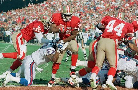 Despite defensive efforts of New York Giants' Corey Miller (57), San Francisco 49ers' Ricky Watters (32) crosses the goal line for a first-quarter touchdown, Saturday Jan.15, 1994 in the NFC conference playoffs at San Francisco's Candlestick Park