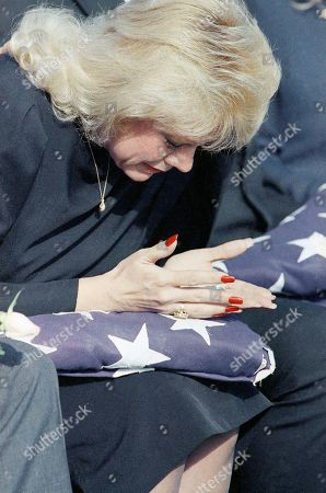 Robin Ann Walker looks at the flag in her lap at the funeral of her son Marine Lance Cpl. Daniel Byron Walker on in Flint, Texas. Walker was the first Texan kille in combat in the Persian Gulf War