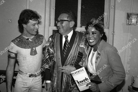 """Henry Kissinger, Andy Gibb, Sharon Brown Former Secretary of State Henry Kissinger tries on singer Andy Gibb's Dream Coat backstage at the Royale Theater in New York, after Gibb's starring performance in """"Joseph and the Amazing Technicolor Dreamcoat."""" At right is Gibb's costar, Sharon Brown"""