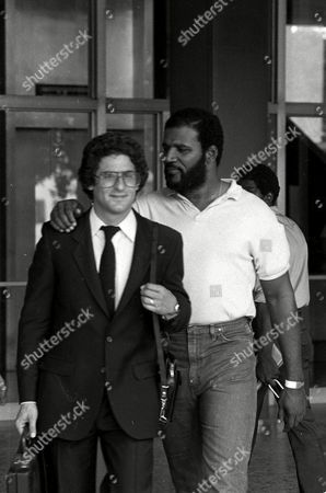 "Stock Image of HOLLYWOOD HENDERSON Former pro football star Thomas ""Hollywood"" Henderson puts his arm around attorney Arnold Barry Gold as they leave a Long Beach, Ca., courtroom . Henderson was scheduled to be arraigned on sex charges involving a 15-year-old girl, but the arraignment was postponed"