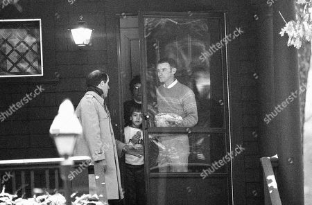 Scott McAuliffe, son of Christa McAuliffe who was killed when the space shuttle Challenger exploded, peers from his front door of his Concord, New Hampshire, home, . Concord police Sgt. John Clark, left, had given a plate of food prepared by a neighbor to an unidentified family member
