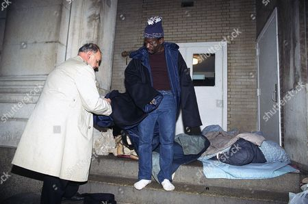 Brother Bill McDonald, left, gives a new coat to Philip Jones, who is homeless, in Philadelphia. The coats called Shelter-Paks, designed and produced by local students, are reversible for wet or dry weather, can be used as a sleeping bag at night and fold up into a carrying case