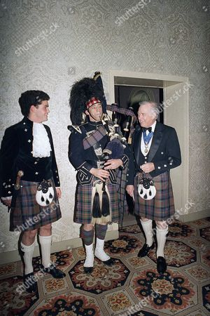 "Stock Picture of Hugh Downs, Charlie Kron, Sadim Young Hugh Downs, right, host of ABC's ""20/20,"" and his grandson Sadim Young, left, watch bagpipe player Charlie Kron of Dobbs Ferry, N.Y. play the pipes at the Scottish Ball, at New York's Plaza Hotel"