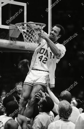 Gary Springer of Iona College is held by teammate as he outs the basket net after Iona won the NCAA Tournament ever Fordham 72-61 at the Meadowlands Arena, East Rutherford N.J. The win gives Iona an automatic bid to the NCAA tournament