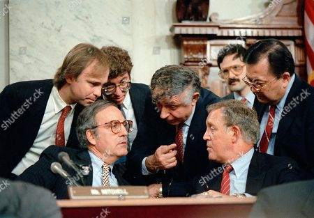 Stock Photo of Arthur Liman, John Nields, George Mitchell, Warren Rudman, Daniel Inouye Arthur Liman, center, chief counsel to the Senate's select committee investigating the Iran-Contra affair, speaks with the House panel's chief counsel, John Nields Jr., left, Senators George Mitchell (D-Me.), seated, second from left, Warren Rudman (R-N.H.), second from right, and Daniel Inouye (D-Hawaii), right, at the conclusion of hearings before the joint House and Senate panels
