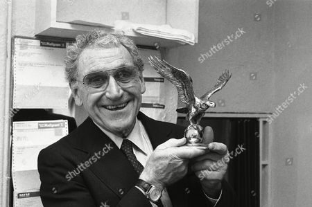 Actor James Whitmore star of Almost an Eagle appears backstage after the opening, New York. The eagle trophy is a gift from producers