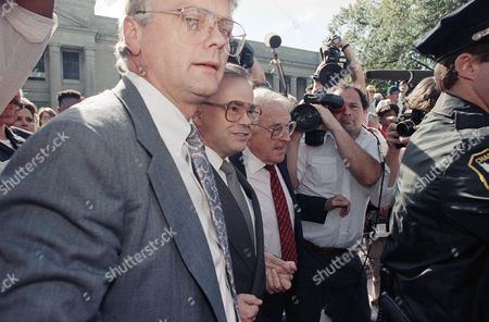 Former PTL leader Jim Bakker (center) is shielded from the press by attorneys Harold Bender, left, and George T. Davis as he leaves the Federal Courthouse in Charlotte, North Carolina, after Bakker was convicted on all 24 counts of fraud and conspiracy. Davis' tie is red
