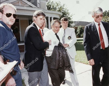 Former PTL leader Jim Bakker (center) is escorted to a car by U.S. Marshals from his attorney's office in Charlotte, North Carolina, . Bakker, who did not appear in court this morning, was taken under order to the State Correctional Institution at Butner, North Carolina, for psychiatric evaluation