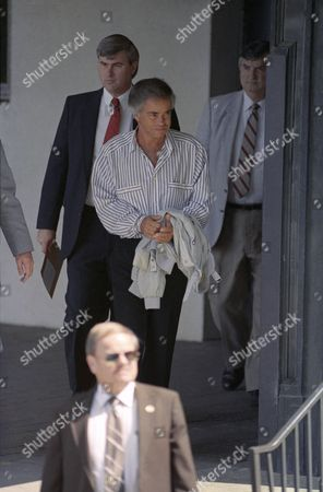 Former PTL leader Jim Bakker is escorted by U.S. Marshals from the Federal Courthouse in Charlotte, North Carolina, after being sentenced to 18 years on his fraud and conspiracy conviction