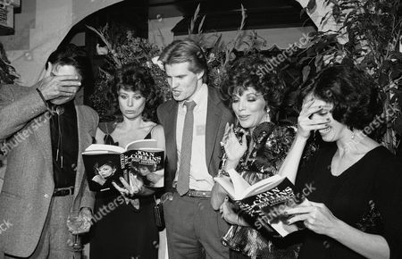 "Actress Joan Collins, second from right, and fellow cast members from the television series ""Dynasty"", look over copies of her autobiographical book ""Past Imperfect"" during a party to celebrate the U.S. release of the book. At the party at night on in Los Angeles were, from left, Michael Nader, Deborah Adair, Jack Coleman, Ms. Collins and Kathleen Beller, Nader and Beller feign embarrassment over passages in the book"