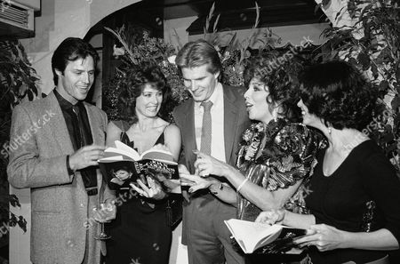 "Stock Photo of Actress Joan Collins, second from right, and fellow cast members from the television series ""Dynasty"", look over copies of her autobiographical book ""Past Imperfect"" during a party to celebrate the U.S. release of the book. At the party at night on in Los Angeles were, from left, Michael Nader, Deborah Adair, Jack Coleman, Ms. Collins and Kathleen Beller, Nader and Beller feign embarrassment over passages in the book"