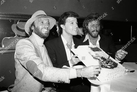 """Singer Andy Gibb, center, holds a cake for his brothers to dig into at a party on in New York after Andy joined the cast of broadway's """"Joseph and Amazing Technicolor Dreamcoat."""" The Gibb brother, Maurice, left, and Barry, right, who are two-thirds of the singing group, the Bee Gees show's first anniversary"""