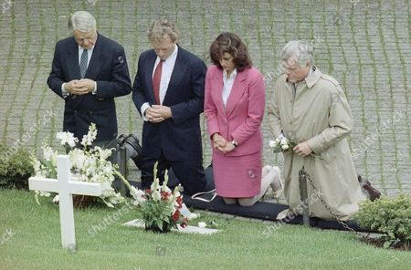 Members of the Kennedy family, Robert Sargent Shriver, left, Rep. Joseph Kennedy, D-Mass., Victoria Reggie, fiancée of Sen. Edward Kennedy, D-Mass., right, kneel at the grave of Robert Kennedy, marking the anniversary of his assassination, Arlington National Cemetery, Arlington, Va. Robert Kennedy was shot on June 5, 1968 in Los Angeles