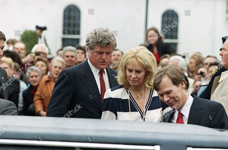 Stock Photo of Sen. Edward Kennedy, left, and his estranged wife Joan Bennett Kennedy, center, walk to a car outside St. Francis Xavier Church for the wedding of Maria Shriver and Arnold Schwarzenegger, Hyannis, Mass. The man on the right is unidentified