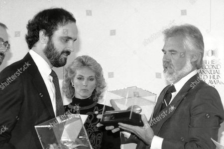 Stock Photo of Singer Kenny Rogers presents a World Media Hunger Award to Walt Bogdanich, left, of the Cleveland Plain Dealer, for best newspaper coverage, at ceremonies in New York, . Marianne Rogers, Kenny's wife, watches the presentation