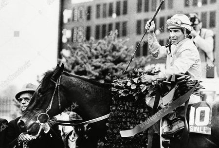 Derby winner Swale, held by trainer Woody Stephens, and with jockey Laffit Pincay, Jr., astride, stands in the winner's circle with his blanket of roses after winning the Kentucky Derby, in Louisville