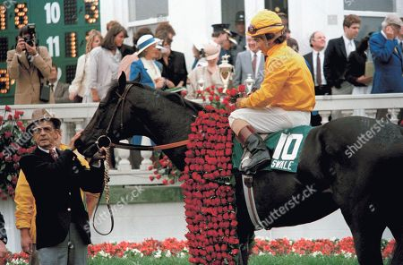 Held by trainer Woody Stephens and with jockey Laffit Pincay, Jr., Astride, Kentucky derby winner swale wears the blanket of roses in the winner's circle at Churchill downs, in Louisville