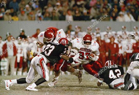 Indiana's Chris Simons bumps South Carolina's Corey Miller out of the way as Anthony Thompson makes a run during Liberty Bowl action in Memphis